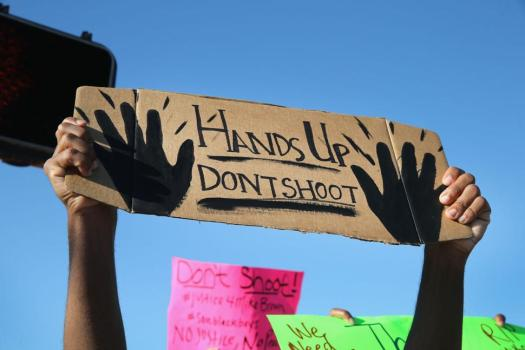 Protesters holding up the universal sign for surrender, which is what witnesses said Brown did before being fatally wounded by Officer Darren Wilson. (Google Images)
