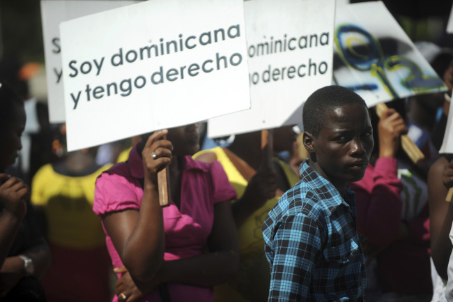 "Hundreds of Dominicans of Haitian origin protest to reclaim their right to their Dominican nationality and to denounce their situation after a 2013 verdict by the Constitutional Tribunal outside the National Congress in Santo Domingo, March 12, 2014. A September 2013 court ruling retroactively denies the Dominican nationality to anyone born after 1929 who does not have at least one parent of Dominican blood, under a constitutional clause declaring all others to be either in the country illegally or ""in transit"". The decision will effectively strip families of Haitian immigrants of their Dominican nationality. The sign reads "" I'm Dominican, and I have rights"". REUTERS/Ricardo Rojas (DOMINICAN REPUBLIC - Tags: POLITICS SOCIETY IMMIGRATION CIVIL UNREST) - RTR3GTXA"