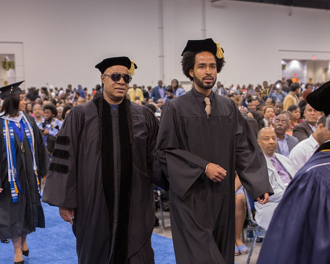 Stevie Wonder is escorted into Spelman College's commencement exercises by his son, Kwame (Photo Credit: Spelman College).